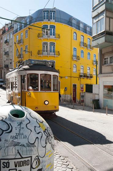 tram Electrico ligne 28 à Lisbonne devant un immeuble jaune